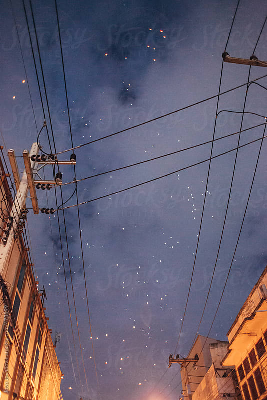 Night time sky and stars with electricity lines and old buildings by Jovo Jovanovic for Stocksy United