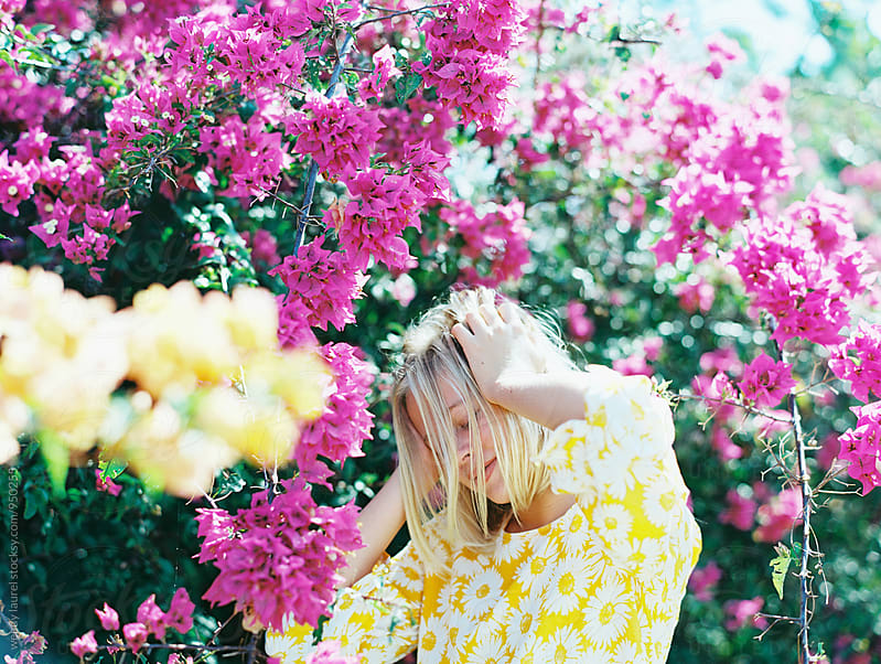 girl holidng head in front of pink flowers wearing yellow dress by wendy laurel for Stocksy United