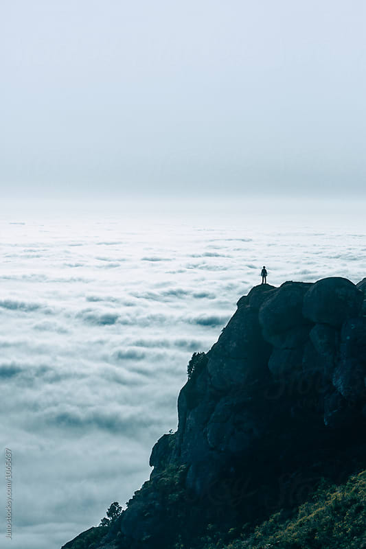 Sillouette of a hiker on a mountain summit overlooking a sea of clouds by Micky Wiswedel for Stocksy United