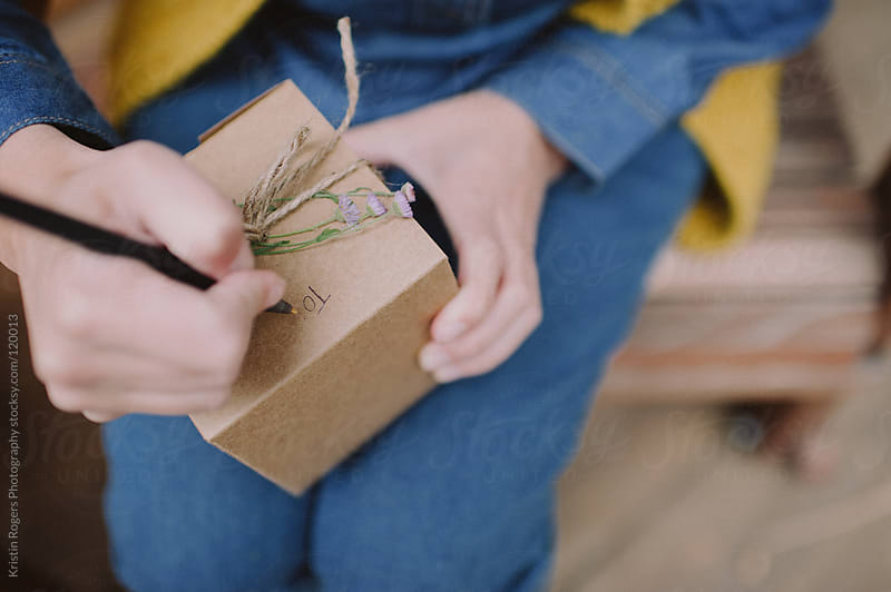 Woman writing To on a gift box by Kristin Rogers Photography for Stocksy United