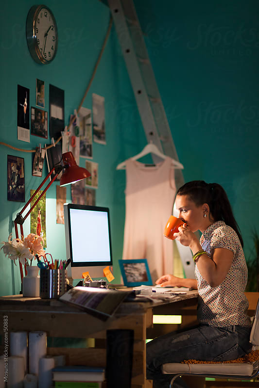 Woman working late at her home office. by Mosuno for Stocksy United
