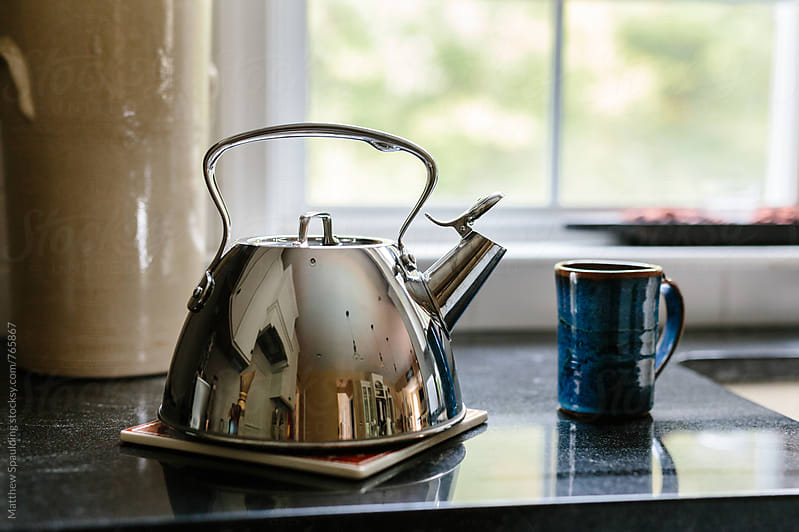 Mug and tea kettle with hot water for drink by Matthew Spaulding for Stocksy United