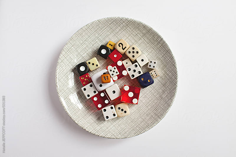 A small dish filled with colourful vintage dice by Natalie JEFFCOTT for Stocksy United
