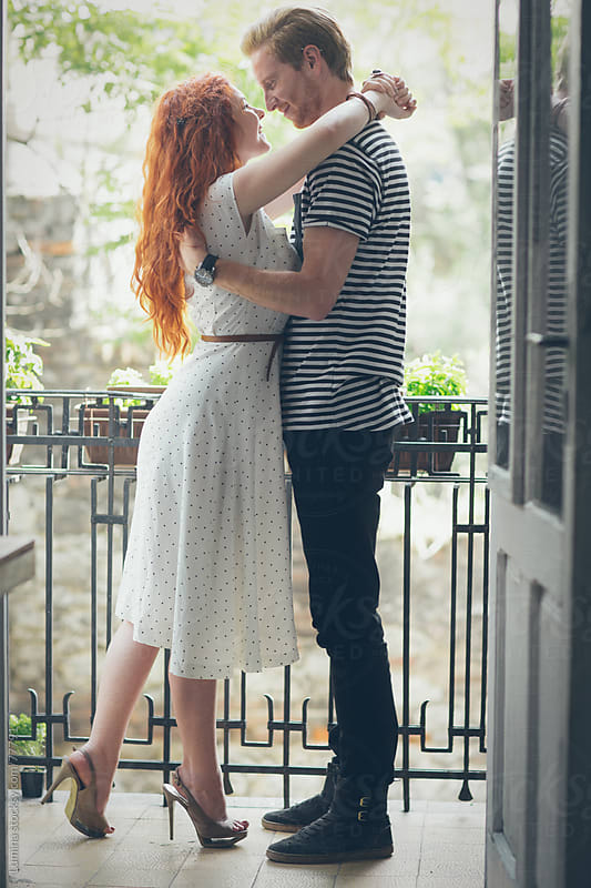 Couple Hugging on a Balcony by Lumina for Stocksy United
