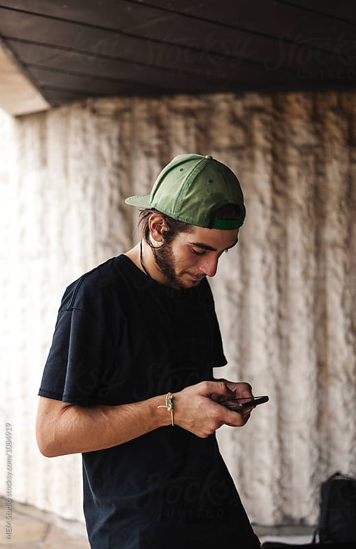 Young man typing on his phone by MEM Studio for Stocksy United