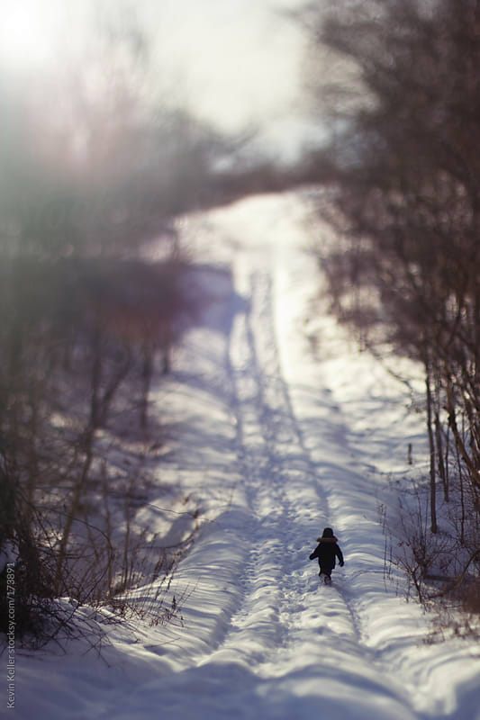 Young Boy Walking Through Snow on a Trail by Kevin Keller for Stocksy United