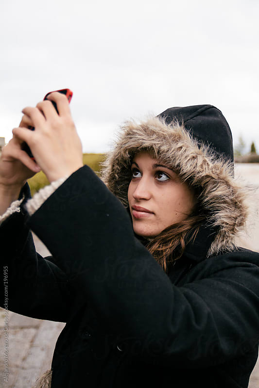 Young woman wearing parka coat and hood taking a photo with her cellphone by Alejandro Moreno de Carlos for Stocksy United