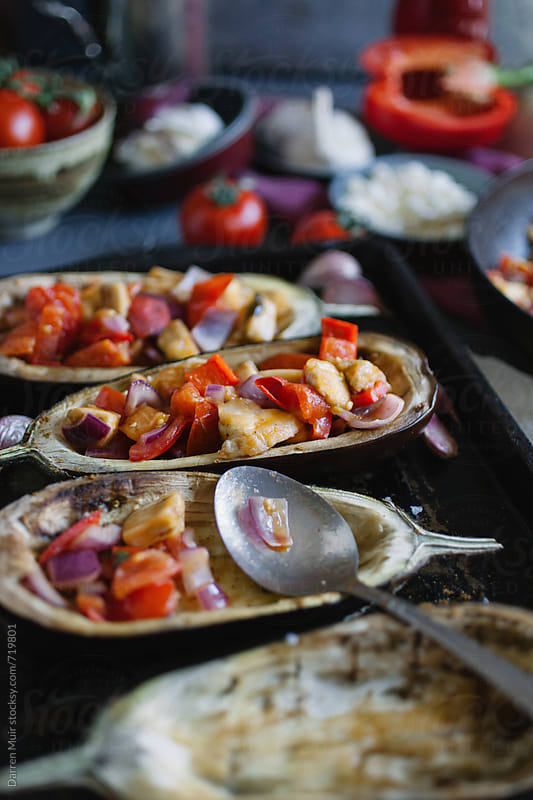 Filling aubergine shells with vegetables and cheese for roasting. by Darren Muir for Stocksy United