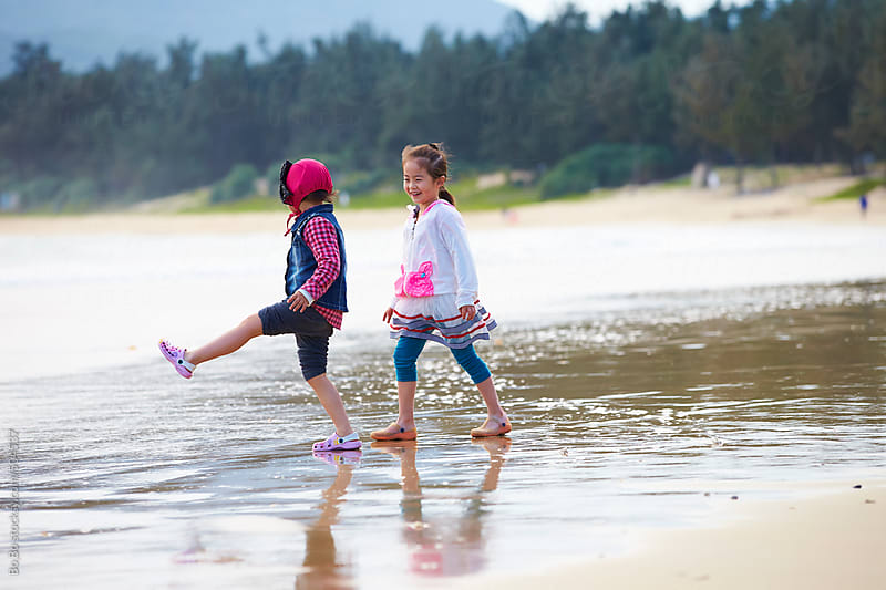 two happy asian little girl playing on the beach by Bo Bo for Stocksy United