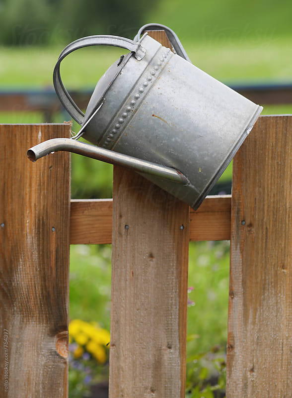 watering can on a fence by rolfo for Stocksy United