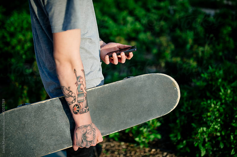 Young skater tattooed giving a walk by Javier Marquez for Stocksy United