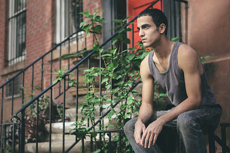 Portrait of a Latino Young Man in a New York Residential Neighborhood by Joselito Briones for Stocksy United