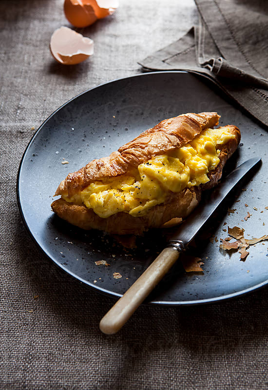Croissant pastry filled with scrambled eggs  by Nadine Greeff for Stocksy United