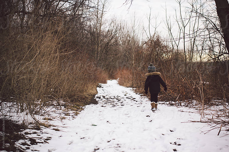 Young Boy Walking Away on a Snow Covered Hiking Trail by Kevin Keller for Stocksy United