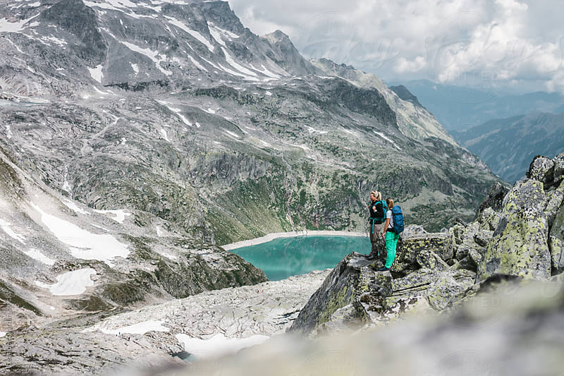 two female hiker standing and overlooking the high alpine glacier scenery by Leander Nardin for Stocksy United