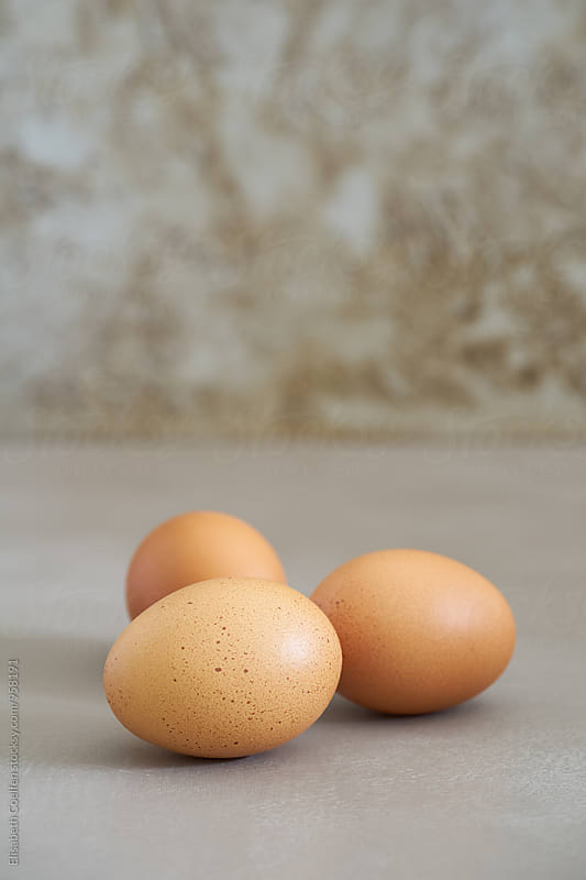 Fresh brown chicken eggs on grey by Elisabeth Coelfen for Stocksy United