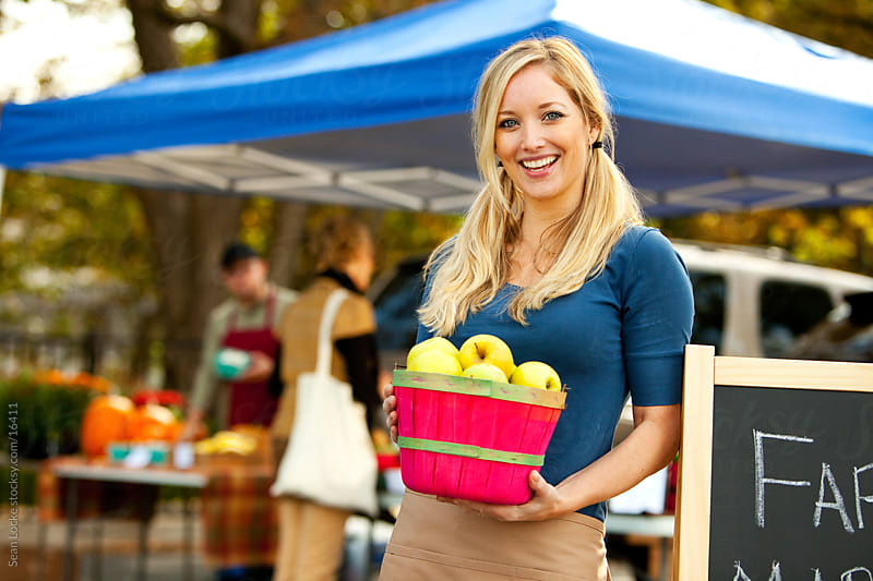 Farmer's Market: Cheerful Seller Holding Apple Basket by Sean Locke for Stocksy United