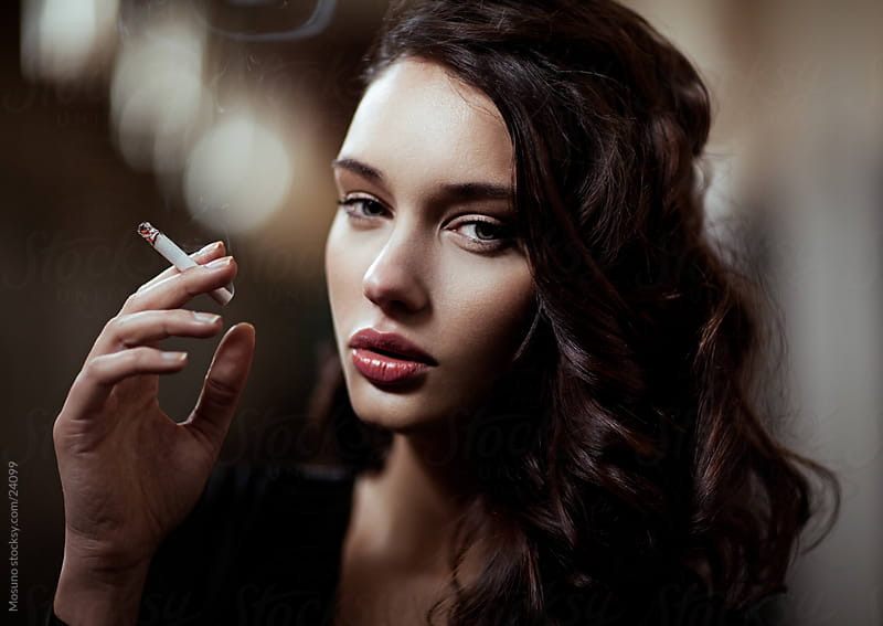 Beautiful woman posing with a cigarette. by Mosuno for Stocksy United