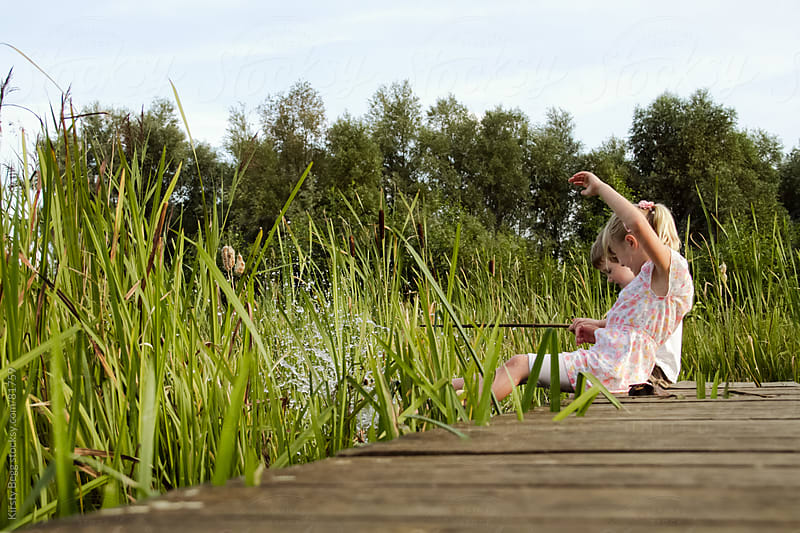 Boy and Girl splashing in pond at nature reserve by Kirsty Begg for Stocksy United