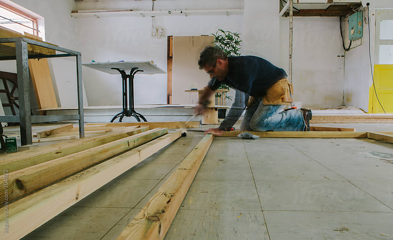 Carpenter fitting a wooden floor by kkgas for Stocksy United