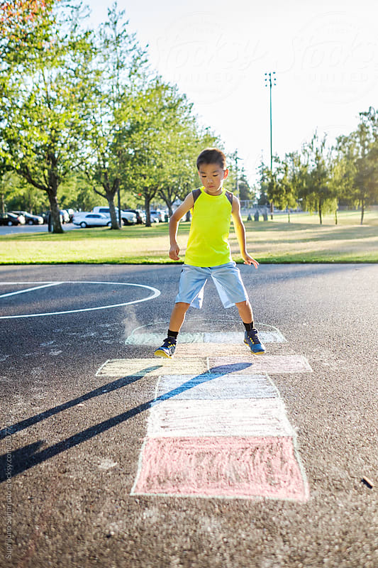 Asian kid playing hopscotch in the playground by Suprijono Suharjoto for Stocksy United