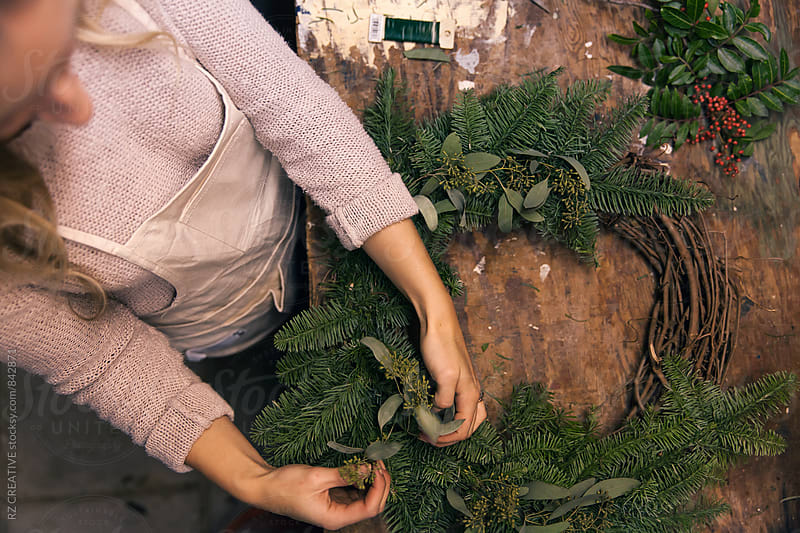 Woman's hands making a holiday wreath in work shop. by RZ CREATIVE for Stocksy United