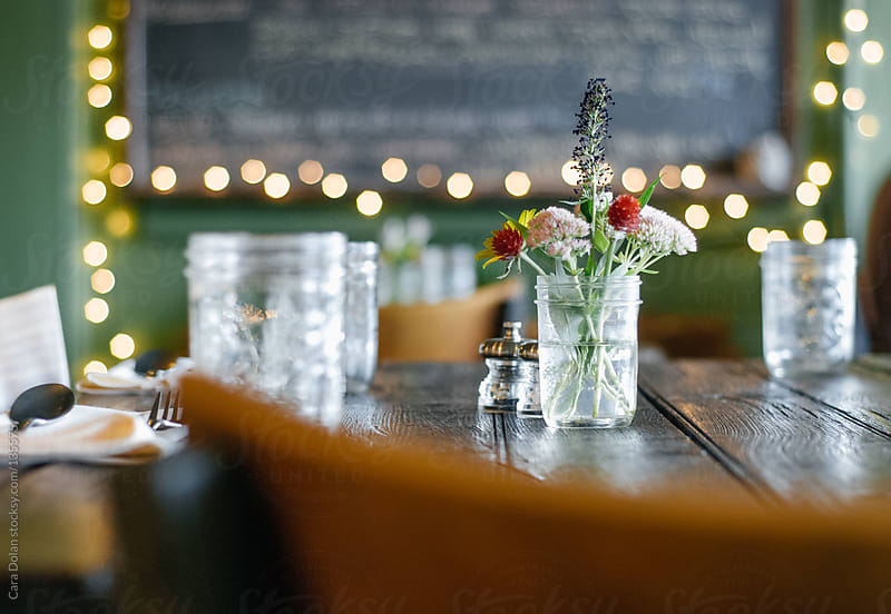 Table setting at a rustic restaurant with jars and floral centerpiece by Cara Dolan for Stocksy United