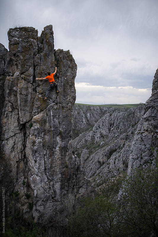 Male climber climbing to the top of a steep rock face by RG&B Images for Stocksy United