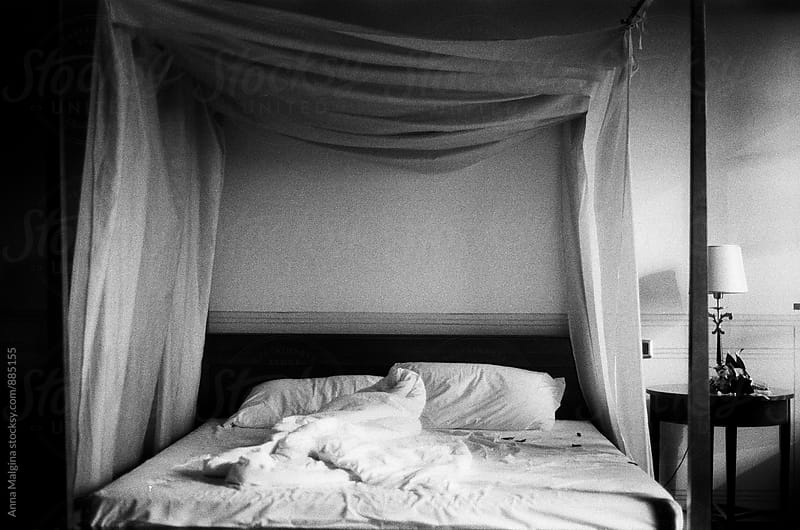 A black and white film photo of white bedroom with king size bed by Anna Malgina for Stocksy United