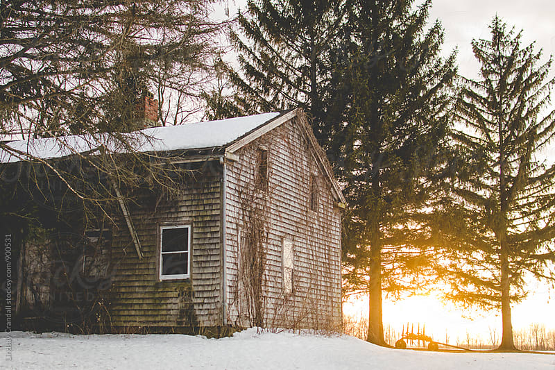 Abandoned house at sunset in the snow by Lindsay Crandall for Stocksy United