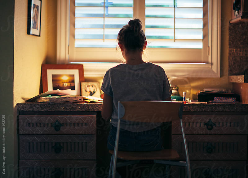 Young girl sitting at a desk in the evening working on homework by Carolyn Lagattuta for Stocksy United