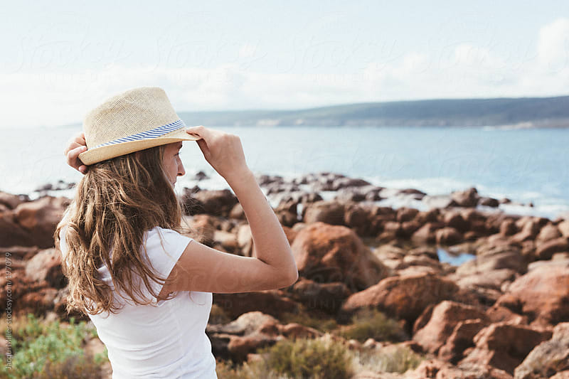 Side view of cute teenage girl holding her hat on her head while looking out at the ocean by Jacqui Miller for Stocksy United