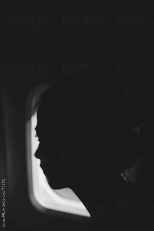Portrait of a young woman looking through an airplane window by Jovana Rikalo for Stocksy United