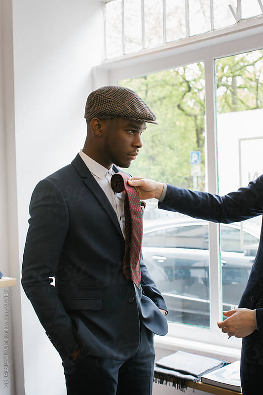 Men's Fashion - Portrait of Stylish Young Black Man Trying on Tie by Julien L. Balmer for Stocksy United