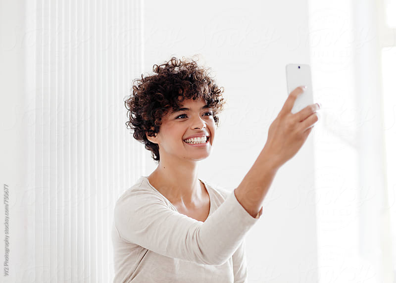 Beautiful young woman taking a selfie photo with phone by W2 Photography for Stocksy United