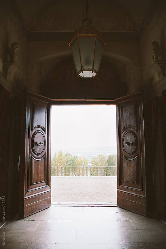View out of  palace doors looking out over Tuscany by Sarah Lalone for Stocksy United