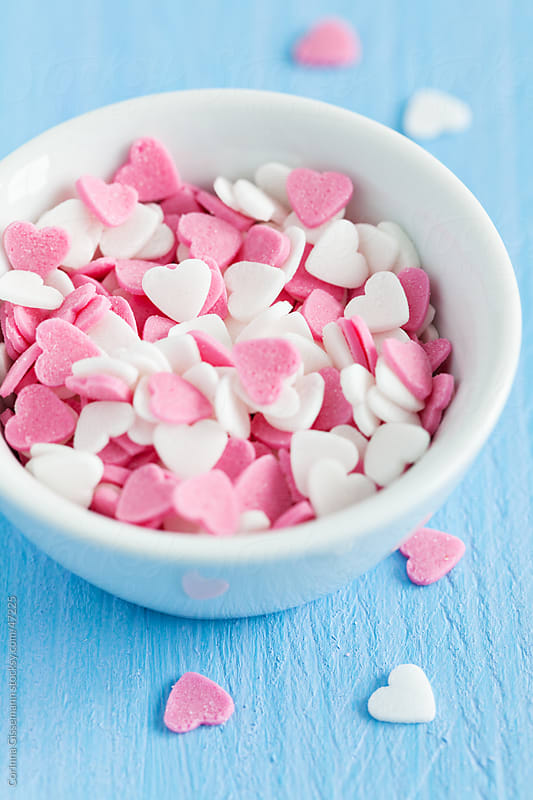 pink and white sugar hearts in a bowl on blue background by Corinna Gissemann for Stocksy United