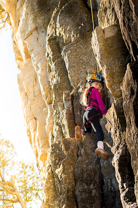 Little Girl Rock Climbing With Sun Flare by JP Danko for Stocksy United