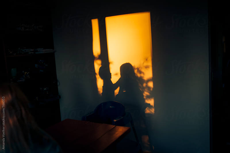 Shadows of young children in evening light by Amanda Voelker for Stocksy United