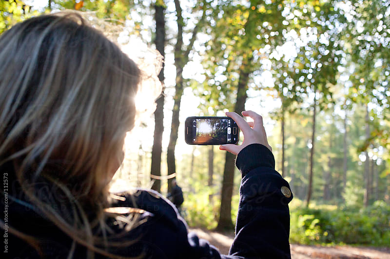 Young blond woman making a photo of a beautiful autumn forest by Ivo de Bruijn for Stocksy United