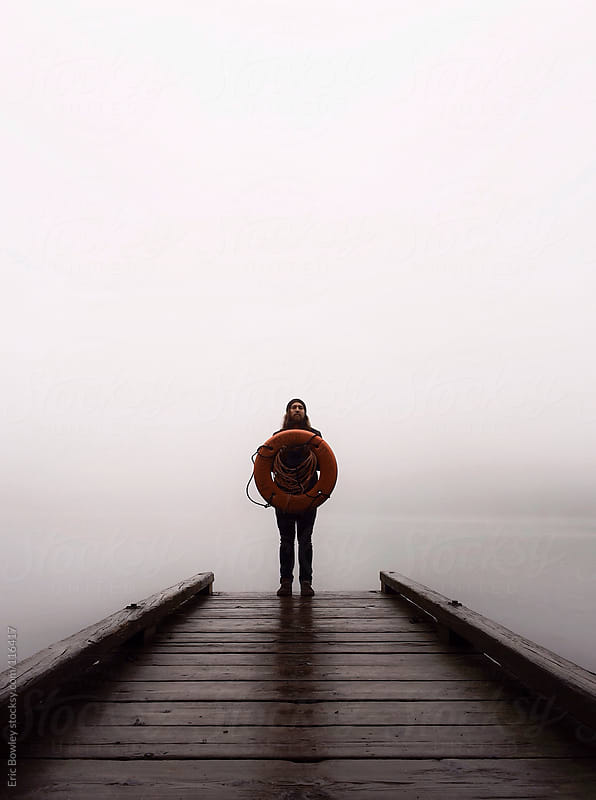 Man Standing On Dock Holding Life Preserver by Eric Bowley for Stocksy United