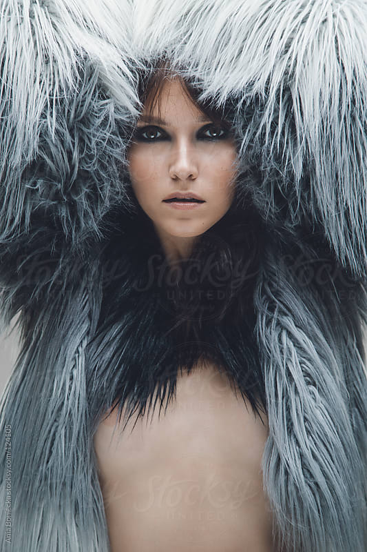 A portrait of a beautiful brunette buried in a faux fur jacket by Ania Boniecka for Stocksy United