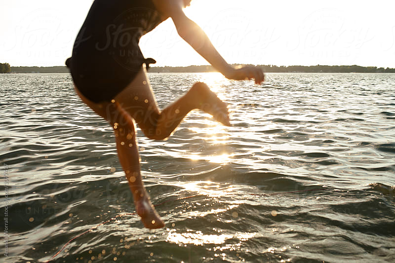 Action shot of anonymous girl jumping into lake at sunset by Amanda Worrall for Stocksy United