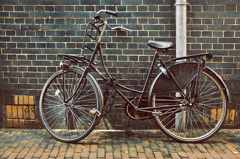 black bicycle against a dark brick wall by Sonja Lekovic for Stocksy United