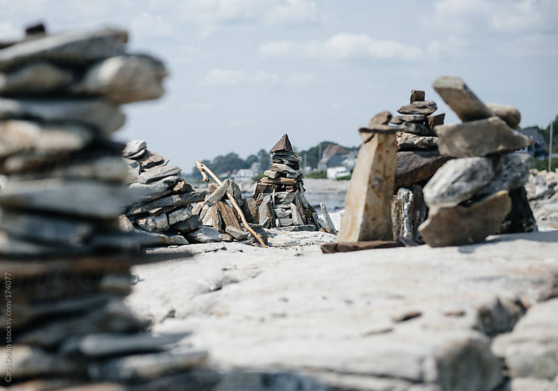Stacked rock sculptures on a large stone surface at the edge of the ocean by Cara Dolan for Stocksy United