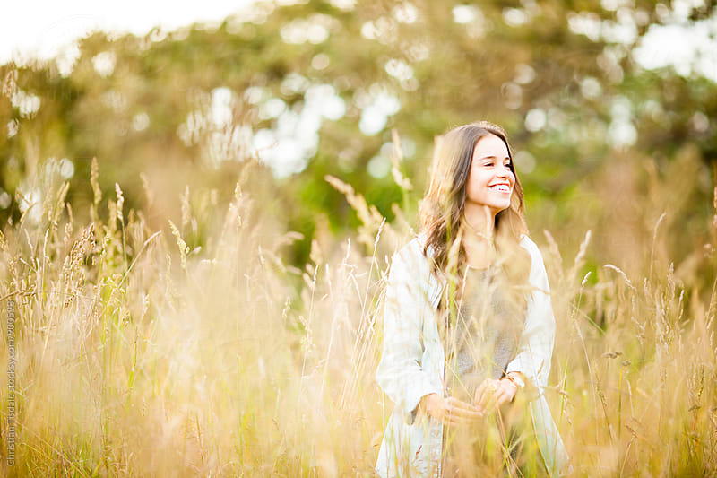 Portrait of a smiling girl in a dry grass field and sunset in summer by Christian Tisdale for Stocksy United