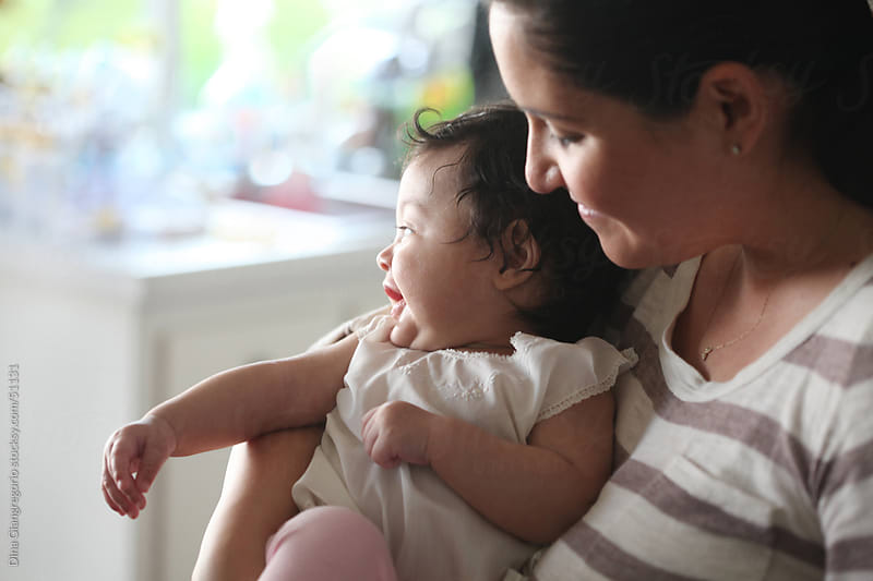 Hispanic mother holding curly dark haired smiling baby showing profile view by Dina Giangregorio for Stocksy United