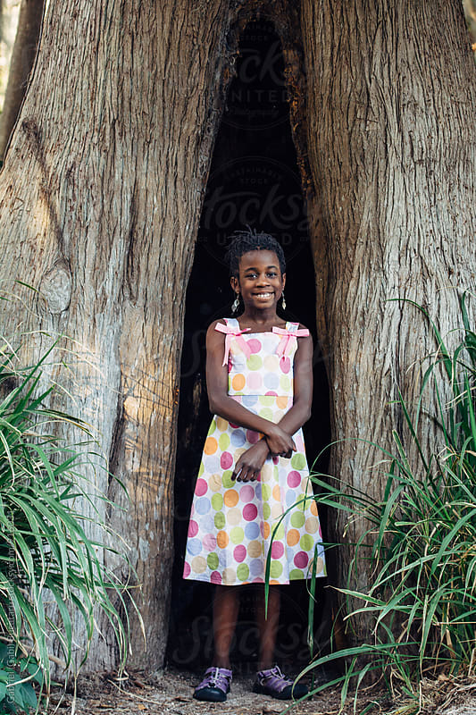 African American girl in a tree hollow by Gabriel (Gabi) Bucataru for Stocksy United