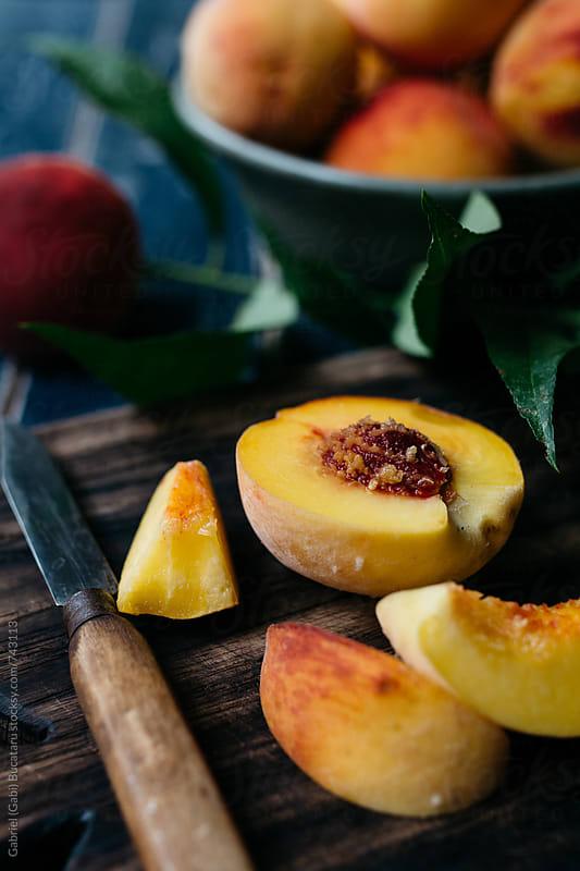 Fresh peach cut up on a chopping board by Gabriel (Gabi) Bucataru for Stocksy United