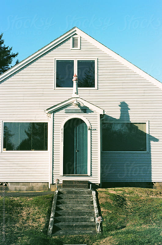 White Building with Windows and Decorative Lighthouse Figure on the Coast of Washington State by Briana Morrison for Stocksy United